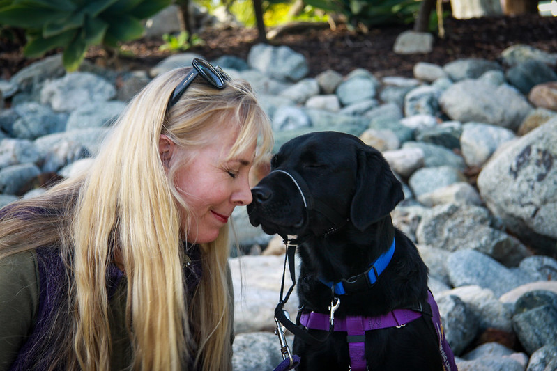 woman and service dog connect face to face with their eyes closed