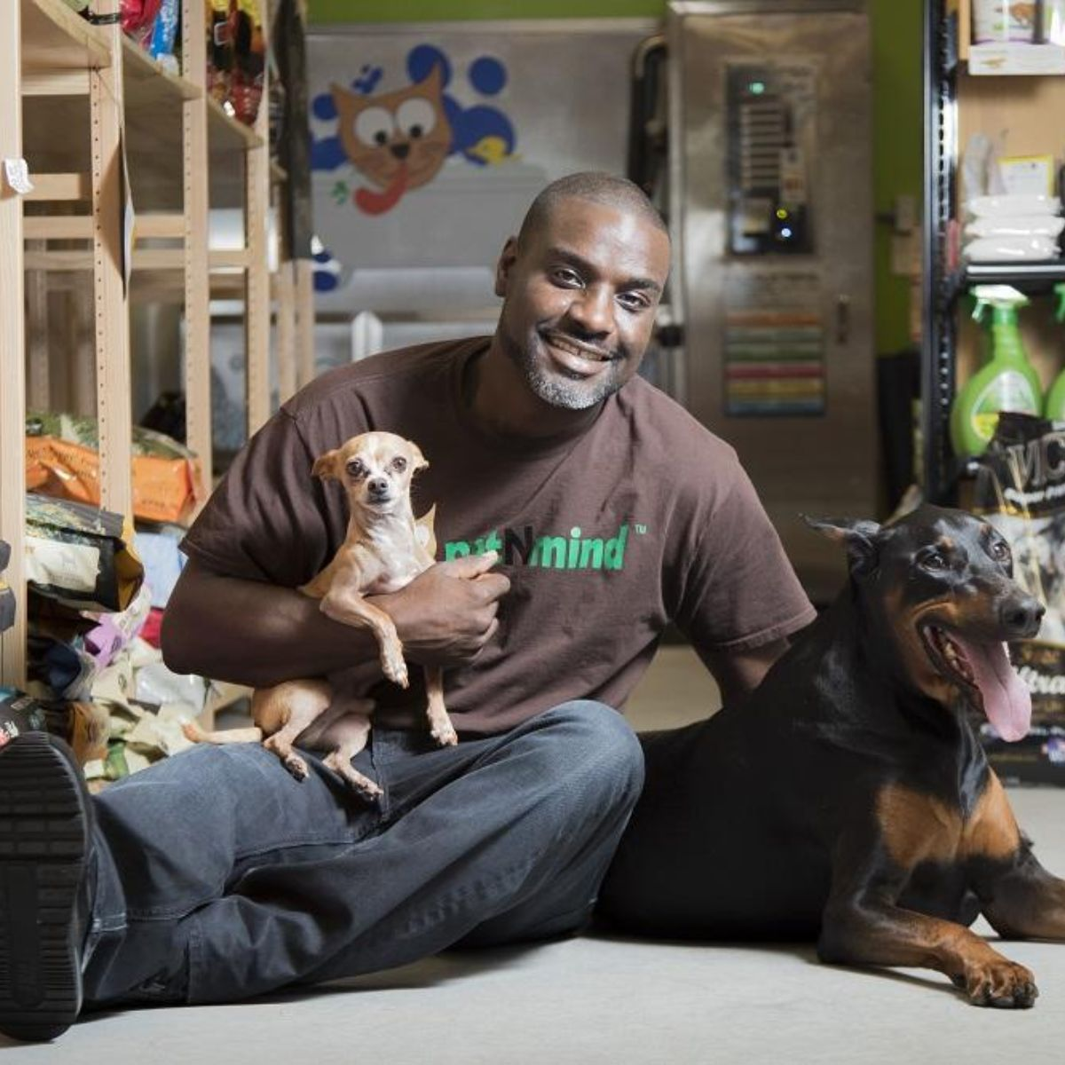 adrian archie sits with his two dogs inside petnmind store